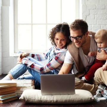 Jong gezin gelukkig in nieuwe woning op de laptop finzie website