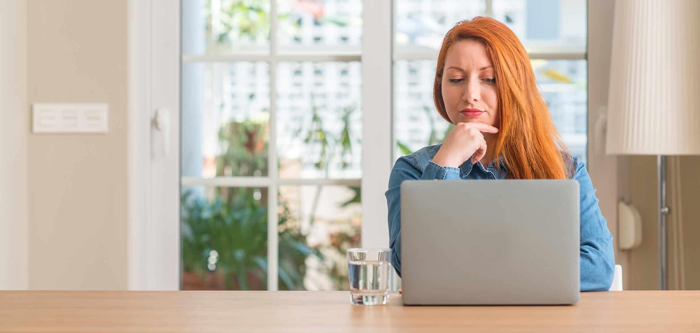 Dame rood haar achter laptop vrouw oranje haar met neuspiercing finzie website