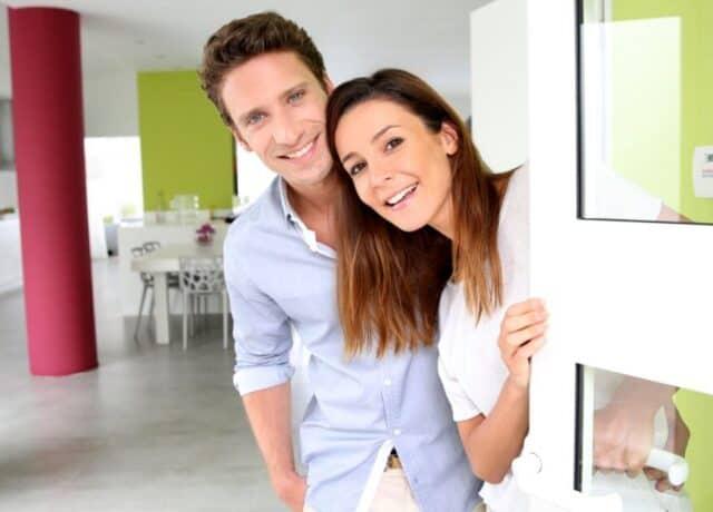 Man en vrouw in woning die naar camera kijken