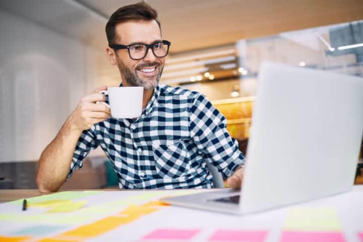 Man met baard en bril lacht naar zijn laptopscherm