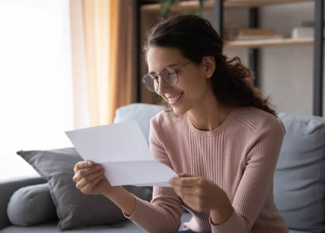 Vrouw bekijkt brief met nieuwe WOZ-waarde