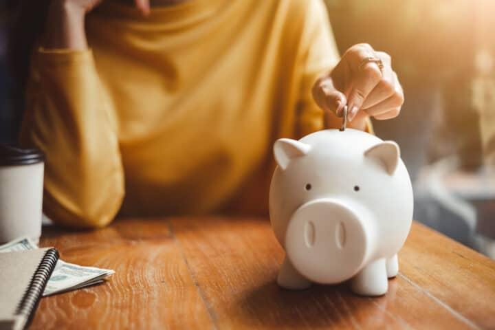 Vrouw spaart het geld dat zij over heeft gehouden aan het einde van de maand.